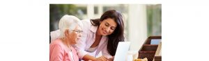 Woman helping older lady work on a laptop